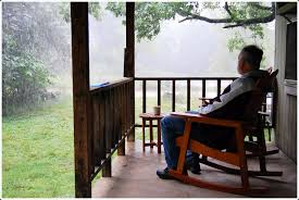 man on porch in rain